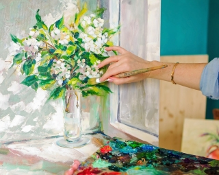 Brush and oil paints on a palette paint a picture of the artist's hands texture mix paint in different colors. Artist holding a palette with paint brushes and palette knife