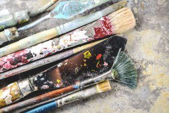 Dirty paint brushes on aluminum tray (Shallow DOF)